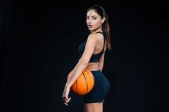Mulher da aptidão que guarda a bola do basquetebol e que olha para trás na câmera fotos de stock