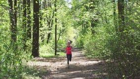 Mulher da aptidão que movimenta-se na floresta ensolarada filme