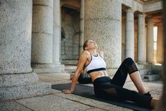 A mulher da aptidão que relaxa em uma esteira de formação após o exercício com olhos fechou-se Atleta fêmea que faz o treinamento imagem de stock