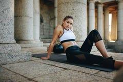 Mulher da aptidão que senta-se em uma esteira da ioga e que relaxa durante o exercício fotos de stock
