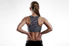 Mulher da aptidão que sofre da dor lombar imagens de stock