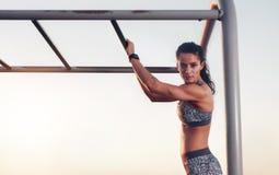 Mulher da aptidão que treina fora em barras de macaco foto de stock royalty free