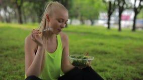 Mulher da aptid?o que come a salada fresca em um parque, alimento saud?vel do vegetariano video estoque