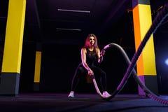 A mulher da aptid?o que usa o treinamento ropes para o exerc?cio no gym O atleta que d? certo com batalha ropes no gym transversa imagem de stock royalty free