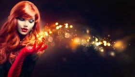 A mulher da beleza com mágica dourada acende em sua mão Foto de Stock Royalty Free