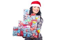 Mulher da beleza no chapéu de Santa que dá presentes Fotografia de Stock