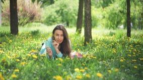 Mulher da beleza no prado rapariga bonita ao ar livre Aprecie a natureza Menina de sorriso saudável que encontra-se na grama verd video estoque