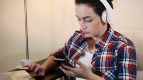 Mulher da beleza que escuta a música em fones de ouvido e que datilografa no smartphone filme