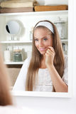 Mulher da beleza que examina sua cara no espelho fotos de stock royalty free