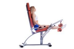 Mulher da beleza que senta-se no exercitador hidráulico alaranjado Fotos de Stock