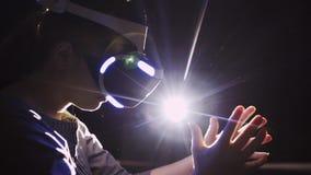 Mulher da colheita nas mãos moventes dos auriculares de VR no espaço escuro abstrato video estoque