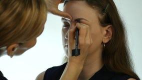 Mulher da composição do olho que aplica o pó da sombra O estilista está fazendo compensa pela fêmea pelo lápis de olho video estoque
