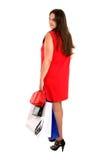 A mulher da compra no vestido vermelho gira para trás Foto de Stock Royalty Free
