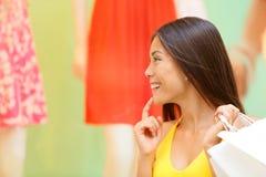 Mulher da compra que olha a exposição da janela na loja Fotos de Stock Royalty Free