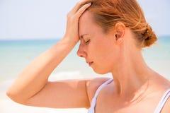 Mulher da dor de cabeça na praia ensolarada Mulher com insolação Perigo quente do sol Problema de saúde no feriado imagem de stock royalty free