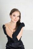 Mulher da elegância em luvas pretas e vestido na luz Sorriso imagem de stock royalty free