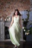 Mulher da elegância no vestido bege longo No interior fotografia de stock