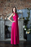 Mulher da elegância no vestido cor-de-rosa longo No interior foto de stock royalty free