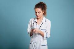 Mulher da enfermeira que datilografa no smartphone seriamente Fotos de Stock