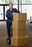 Mulher da entrega que levanta com a pilha de caixas Fotografia de Stock Royalty Free