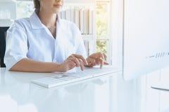 Mulher da estudante de Medicina da mão que usa o teclado de computador na mesa na sala do escritório, fim de datilografia do dedo fotos de stock royalty free