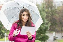 Mulher da felicidade com guarda-chuva e tablet pc no parque imagens de stock