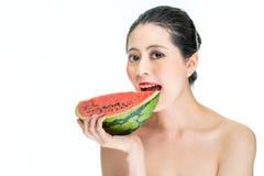 A mulher da forma aprecia comer a melancia com os bordos vermelhos, saborosos, mordida Imagens de Stock