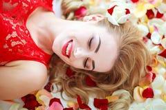 Mulher da forma da beleza do retrato em termas das pétalas da flor Fotografia de Stock