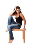 Mulher da forma com assento das calças de brim Fotografia de Stock Royalty Free