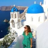 Mulher da forma de Santorini que visita Oia, vila branca famosa com as abóbadas azuis em Grécia Menina no vestido e em óculos de  fotos de stock royalty free