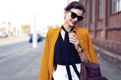 Mulher da forma do retrato nos ?culos de sol que anda na rua Veste o revestimento amarelo, sorrindo para tomar partido foto de stock