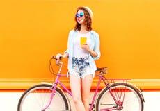 A mulher da forma do verão com o copo do café ou do suco e o vintage retro bicycle Fotografia de Stock