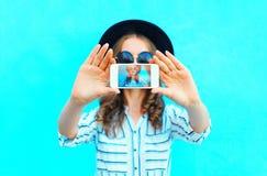 A mulher da forma está tomando o autorretrato da foto em um smartphone na tela do close up da cidade sobre o azul colorido Imagem de Stock