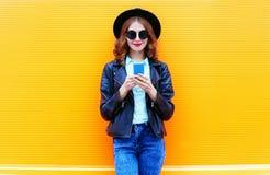 A mulher da forma está usando o smartphone no revestimento preto da rocha Fotografia de Stock