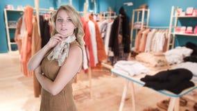 A mulher da forma na loja de roupa em retalhos luxuosos bonitos do shopping do borrão do sumário armazena o fundo obscuro interio fotos de stock royalty free