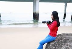 Mulher da fotografia da mulher que aprende a fotografia na praia do beira-mar foto de stock