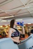 Mulher da ginástica que elabora a posição feliz de sorriso da água bebendo por máquinas da aptidão do moonwalker Misturado novo d imagem de stock royalty free