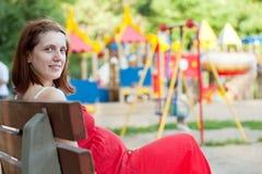 Mulher da gravidez contra o campo de jogos Imagens de Stock Royalty Free