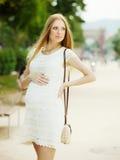 Mulher da gravidez contra a rua do verão Imagens de Stock Royalty Free