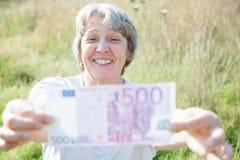 Mulher da idade avançada que guarda cinco cem euro imagens de stock