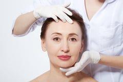 Mulher da Idade Média que obtém o tratamento dos termas Massagem de cara Botox e colagênio antienvelhecimento O conceito da cirur fotos de stock