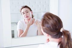 Mulher da Idade Média que olha no espelho na cara Enrugamentos e conceito antienvelhecimento dos cuidados com a pele Foco seletiv fotografia de stock