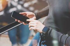 Mulher da imagem que trabalha o estúdio moderno, mão esperta vestindo do relógio do projeto genérico Móbil vazio tocante da tela  Imagem de Stock