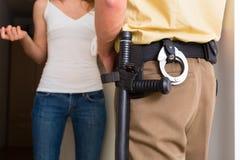 Mulher da interrogação do agente da polícia na porta da rua Imagens de Stock