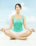 A mulher da ioga medita o assento na pose dos lótus sobre o céu imagens de stock