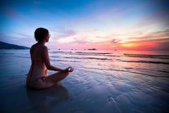 Mulher da ioga na costa de mar Fotos de Stock Royalty Free