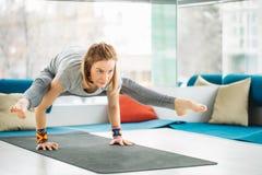 A mulher da ioga que faz a pose do pino do equilíbrio exercita no gym imagem de stock