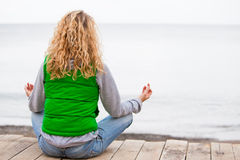 Mulher da ioga que senta-se na ponte de madeira perto do oceano Fotografia de Stock Royalty Free