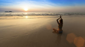 Mulher da ioga que senta-se na pose dos lótus na praia durante por do sol surpreendente Foto de Stock