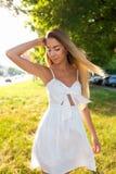 A mulher da luz e da mola, uma menina bonita e feliz em um vestido branco, endireitam os cabelos longos no vento, no verão dentro imagem de stock